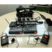 Die Übertragungstechnik:  Die Kamera Panasonic HDC Z10000 im Bild hinten ist über eine 5GHz-Strecke mit einem HDMI - H.265-Enkoder mitte-links auf dem Brett verbunden. Der Ton wird von zwei Funksendern vor dem Brett im 865MHz-Bereich zu den Empfängern vorne auf dem Brett übertragen. Alle Komponenten sind transportsicher auf dem Brett fixiert, können aber ohne Werkzeug entnommen werde. Bei Bedarf ist auch Akku-Betrieb und Upstream über WLAN möglich.